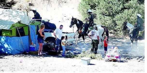 BRAD HORN/Nevada Appeal Transients including Michael Hesse, center with back turned, watch as Carson City sheriff's deputies leave their campsite after warning them they have one week to vacate the area or face trespassing charges. Below, an unidentified couple comfort each other with a hug after the warning.