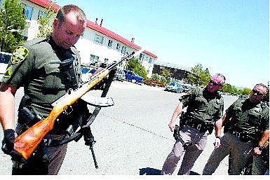 BRAD HORN/Nevada Appeal Carson City Sheriff Deputy Gary H. Underhill holds the SKS Russian assault rifle that was fired twice from an apartment's balcony in Carson CIty on Saturday. Below is suspect Manual Vargas-Rangel, 41, who was arrested on suspicion of firing an assault rifle near children at a swimming pool.