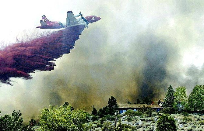 Cathleen Allison/Nevada Appeal An air tanker from Battle Mountain drops slurry on  the houses in Kings Canyon Wednesday during the Waterfall Fire.