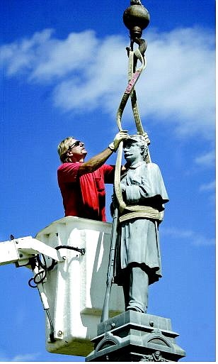 Cathleen Allison/Nevada Appeal Mike Thornton of Connolly Crane secures a 113-year-old statue at the Civil War monument at the Lone Mountain Cemetery Monday morning. The statue will be sent to Cincinnati for repairs and restoration.