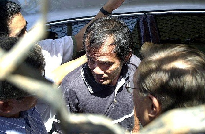 Filipino Angelo dela Cruz, who had been held hostage in Iraq enters the Philippines embassy after he had earlier been handed over to the United Arab Emirates embassy in Baghdad, Iraq, Tuesday July 20, 2004. The hostage drama that has gripped the Philippines for two weeks came to a happy ending Tuesday when insurgents in Iraq freed a Filipino truck driver who has become a national icon at home. (AP Photo/Mohammed Uraibi)