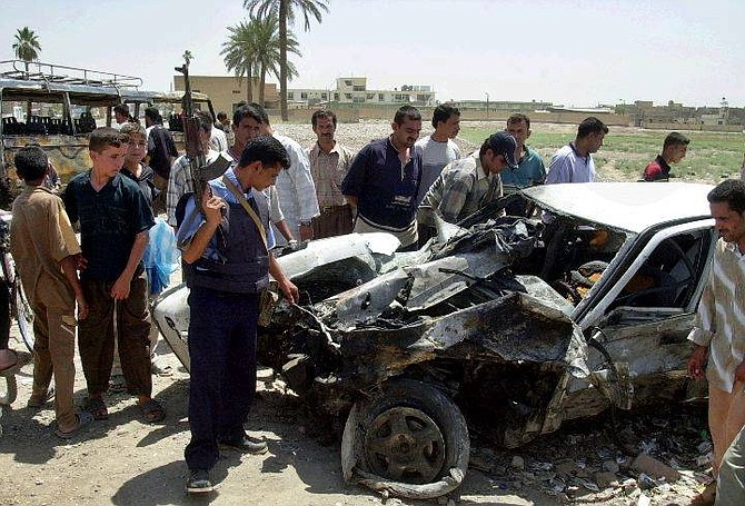 Civilians and Iraqi police inspect the charred vehicles left after a car bomb blew up in Baqouba, some 65 kms northeast of Baghdad, Wednesday July 28, 2004. A suicide attacker killed at least 51 people when he exploded a bomb-laden vehicle outside a central Baqouba police station Wednesday, a top police official said. (AP Photo/Karim Kadim)