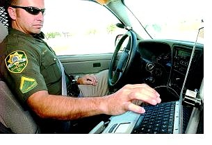 Carson City Sheriff's Deputy Gary Underhill checks his Mobile Data Computer  during a call Wednesday.                                  Rick Gunn Nevada Appeal