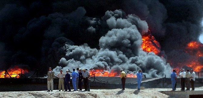 Foreign and Iraqi oil workers look at a flames and a large plume of smoke rising after an attack on an oil pipeline in al-Barjisiya, 30 km (18 miles) southwest of Basra, Iraq Thursday Aug. 26, 2004. Oil official says saboteurs attacked multiple pipelines in southern Iraq. (AP Photo/Nabil al Jurani)