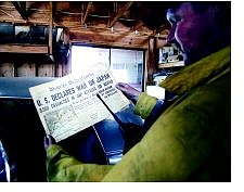 BRAD HORN/Nevada Appeal Stan Heinrichs, the superintendent for Morning Star Hot Shots, of Carson City holds up a newspaper found in one of the classic cars housed in Jerry Wright's garage at the top of Pinion Road on Thursday.