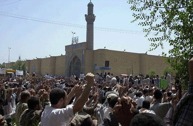 Supporters of rebel Shiite cleric Muqtada al-Sadr shout slogans in his favor before offering prayer outside the Kufa mosque in Kufa, Iraq, Friday Sept. 3, 2004. Iraqi security forces fired warning shots and barred vehicle traffic leading to Kufa on Friday, fearing an outbreak of violence as hundreds of worshippers descended on the holy city for the first weekly prayers since al-Sadr relinquished control of its revered shrine under a peace deal. (AP Photo/Alaa al Murjani)