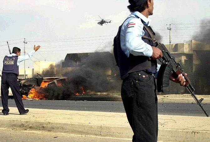 Iraqi police stand  near a burning US military vehicle after it came under attack in the center of Mosul, north of Baghdad, Iraq, Wednesday, Oct 13, 2004. (AP Photo/Mohammed Ibrahim)