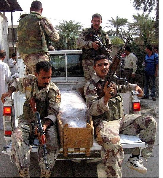 Iraqi national guardsmen arrived with a body of a killed comrade to the morgue in Baqouba, north-east of Baghdad, Iraq, Monday, Oct. 25, 2004. The bodies of about 50 Iraqi soldiers were found on a remote road in eastern Iraq on Sunday. (AP Photo/Sami Aburaya)