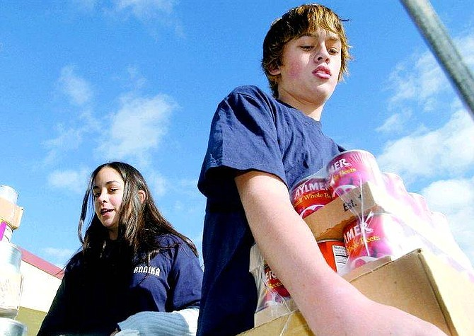 Rick Gunn/Nevada Appeal Carson Middle School students Annika Chryssos, 13, and Levi Masterson, 13, load canned goods on the FISH truck Wednesday at the school.