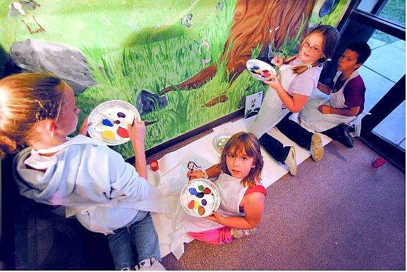 Brad Horn/Nevada Appeal Boys & Girls Club of Carson City members Melyssa Schachten, 12, left, Chainey Gonzales, 8, Sierra Whitton, 12, and Aaron Rumsey, 9, finish the mural at the Southgate Apartment Complex Recreation Center with fairies and other details Friday.