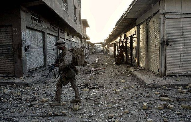 A US Marine of the 1st division walks through the deserted western part of Fallujah, Iraq, Monday, Nov. 15, 2004. U.S. ground forces were trying to corner the remaining resistance in the city. (AP Photo/Anja Niedringhaus)