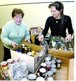 Cathleen Allison/Nevada Appeal Carson City Library staff members Gerry Pearson, left, and Elaine Werlinger sort through some of the food donated to the library in exchange for overdue book fines.  The Food for Fines drive continues until Nov. 24.