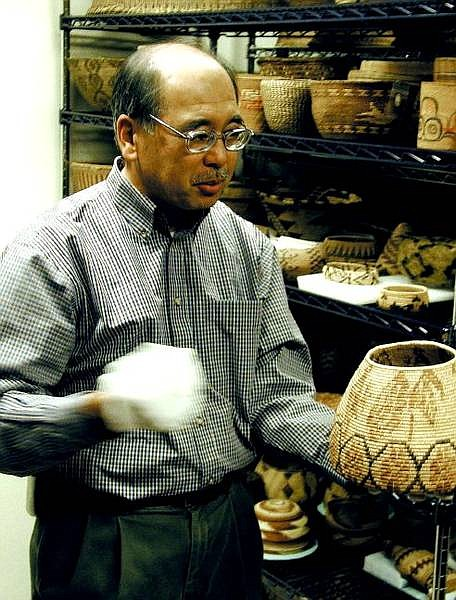 Eugene M. Hattori, Ph.D, curator of anthropology for the Nevada State Museum, displays one of more than 1,200 American Indian baskets in the downstairs vault at the museum.  Peter Thompson/ Nevada Appeal