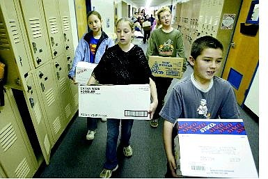 Cathleen Allison/Nevada Appeal Bordewich-Bray Elementary School students, from left, Annie Crounse, Eliza Matley, Andrew Peckham and Jerry Gifford carry boxes of supplies that will be shipped to troops in Kuwait. Bordewich-Bray students collected more than 30 boxes of items, ranging from candy to sports equipment to DVDs.