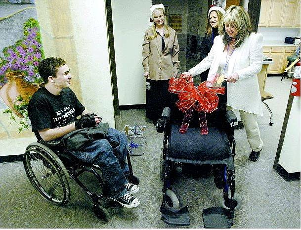 Cathleen Allison/Nevada Appeal Carson High School senior Kevin Petersen, 17, receives a new wheelchair from Capitol City Loans elves, from center, Jennifer Brooks, Maria Torres and Theresa Ohl on Friday at the high school.