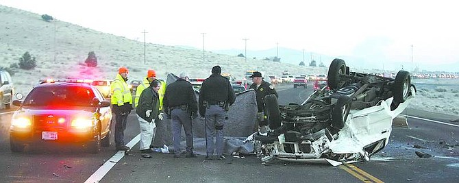 BRAD HORN/Nevada AppealNevada Highway Patrol troopers, a Carson City coroner, and Department of Transportation employees work the scene of a fatal accident that claimed the life of two men this morning on Highway 50.