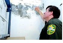 Lt. Ray Saylo of the Carson City Sheriff's Department points out an area of mold on the wall in the  evidence room in the basement of the sheriff's  building.  Rick Gunn Nevada Appeal