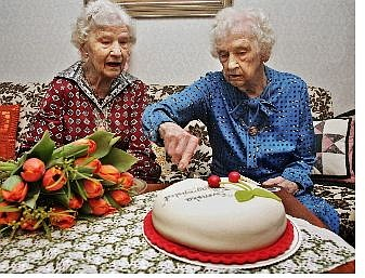 Twins Gunhild Gaellstedt, left, and Siri Ingvarsson cut their 100th anniversary birthday cake in Stockholm, Sweden, Friday. Sweden's oldest living pair of twins, they still do all their shopping, cooking and cleaning by themselves. Associated Press