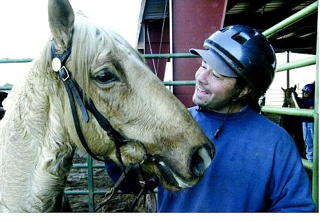 Cathleen Allison/Nevada Appeal Ron Abbott talks with Trigger Wednesday afternoon at the horse arena at Warm Springs Correctional Center. The Comstock Wild Horse Program turns wild horses into rideable mounts that are then adopted at quarterly auctions at the facility.