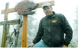 Tim Lampe stands near the cross his  family erected on the site where his parents were killed 41 years ago Tuesday.