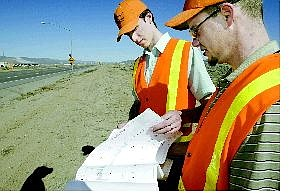 NDOT workers Devin Cartwright, left, and Kevin Maxwell talk about the plans to widen  Highway 50 East (below) from Fortune Drive to Chaves Road on Wednesday afternoon.  Photos by  Cathleen Allison Nevada Appeal