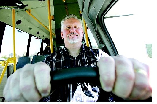 BRAD HORN/Nevada Appeal Mike Delude, the new transit planner for Carson City, poses in the driver's seat of one of the fleet of buses Thursday.