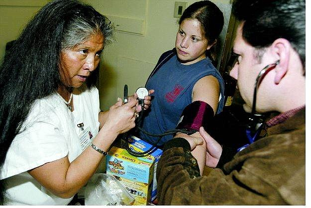 Dan Thrift/Nevada Appeal Western Nevada Community College nursing student Angela Oldridge, left, shows Ted Rupert and his daughter Andria of Carson City how to administer a blood pressure test. Rupert's grandmother has diabetes and was learning how to care for her at the Social Pow-Wow & Health and Wellness fair on Saturday at the Stewart Gym. BELOW LEFT: Dillion Bever, 13, sees the effects of smoking on the lungs at a demonstration by the American Lung Association during the pow-wow.