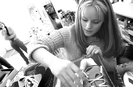 Rick Gunn/Nevada Appeal Shawna Ellis, 17, looks over one of 42 pairs of shoes she purchased from Payless Shoe Source on Topsy Lane on Tuesday. She is collecting the shoes for needy high school students as part of her senior project.