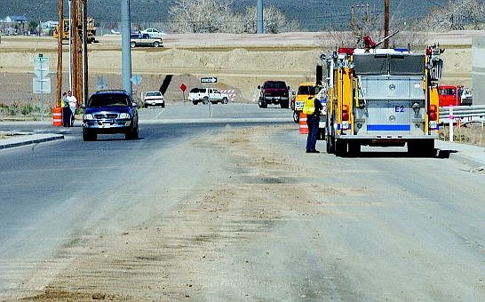 Rick Gunn/Nevada Appeal Firefighters help with traffic during the cleanup of an oil spill at north end of Roop Street near College Parkway, which was closed Tuesday afternoon between Roop Street and Goni Road.