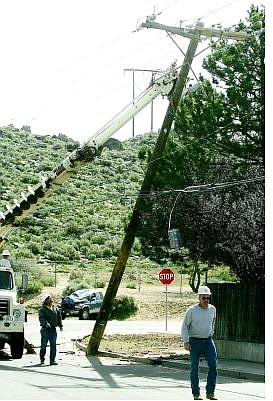BRAD HORN/Nevada Appeal Utility workers repair a power pole at the corner of Roop Street and Winnie Lane after an accident involving a truck on Monday morning.