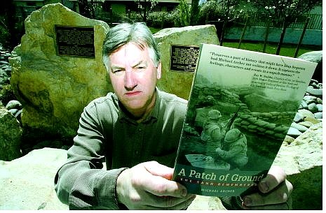 BRAD HORN/Nevada Appeal Michael Archer holds his book, 'A Patch of Ground,' at the Vietnam Memorial at Mills Park on  Friday.