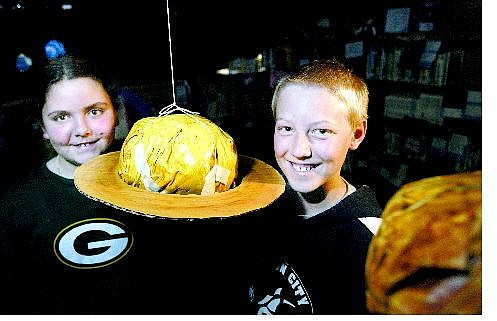 Cathleen Allison/Nevada Appeal Bordewich-Bray Elementary School fifth-graders Siara Hassey and Jace Carlson, both 11, stand in the solar system they helped create out of papier-mâché and duct tape. Fifth-graders are using the display in the school library to teach younger students about the planets.