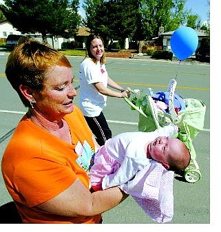 BRAD HORN/Nevada Appeal Linda Martin holds her 3-week-old granddaughter Kaitlynn Glory Plummer while the proud mother Gena pushes her stroller during the March of Dimes Walk in Carson City on Saturday morning. Kaitlynn was born one week premature.