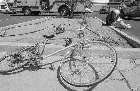 Rick Gunn/Nevada Appeal The driver of a vehicle that struck a bicyclist fills out a report near the Grocery Outlet Tuesday afternoon. The bicyclist was transported by ambulance to Carson-Tahoe  Hospital.