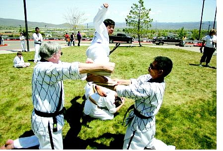 Ralph Seiler, left, and Grandmaster Chi hold a wooden board while 14-year-old, second-degree black belt Dennis Seiler splits the piece in half during the Multicultural Festival at Western Nevada Community College on Saturday.   BRAD HORN/ NEVADA APPEAL