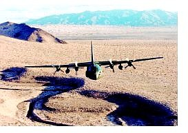"""Nevada Air Guard photo The """"City of Carson City"""" C-130 Hercules airplane flies low over the Nevada desert during training."""