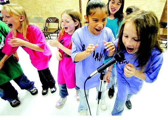 """BRAD HORN/Nevada Appeal From left, Casey Cathey, 8, Anali Diaz, 11, and Yesenia Garcia, 8, react to 10-year-old Kelly Guzzetta's poetry reading at Mark Twain Elementary school during rehearsal on Thursday. First-grade teacher Tracy Schmid has been leading 22 students in the """"Poetry Alive"""" program."""