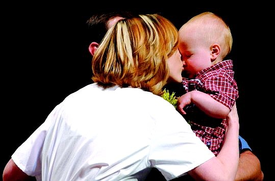 Rick Gunn/Nevada Appeal Tana O'Brien, left, kisses her son, Jake, onstage during the Western Nevada Community College Nurse Pinning Ceremony at the Carson City Community Center on Tuesday. Her husband, Carson City firefighter Scott O'Brien, stands behind.