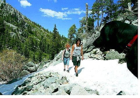 Chad Lundquist/Appeal News service North Lake Tahoe resident Marain Fernald and her friend, Rosie Bernhard, from Boston, hike Eagle Falls on Thursday afternoon with their four-legged friend, Huck. Many high country trails still have snow on them.