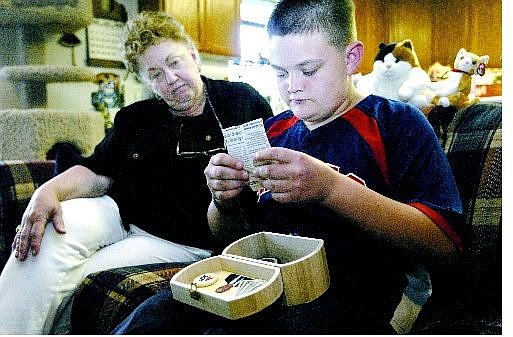 Kyle Matsko, 13, sorts through a memory box he made for his grandfather, Donald Revelle, with his grandmother Nellie Revelle at her Dayton home Wednesday. They received hospice care during her husband's illness.    Cathleen Allison Nevada Appeal