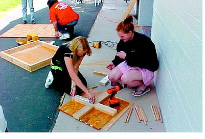 Photo submitted Ashley Young and Lindsay Hammers drill holes into a version of quoits that uses five stakes.