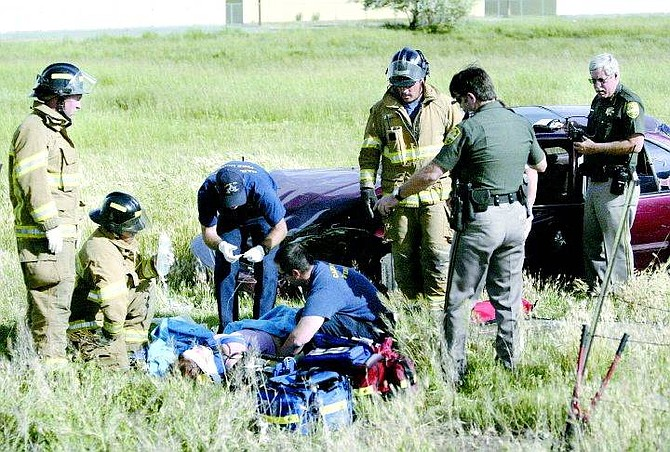 Cathleen Allison/Nevada Appeal Carson City firefighters treat a woman following a rollover accident on Fifth Street on Wednesday afternoon near the Nevada State Prison. She was taken to Washoe Medical Center by Care Flight.