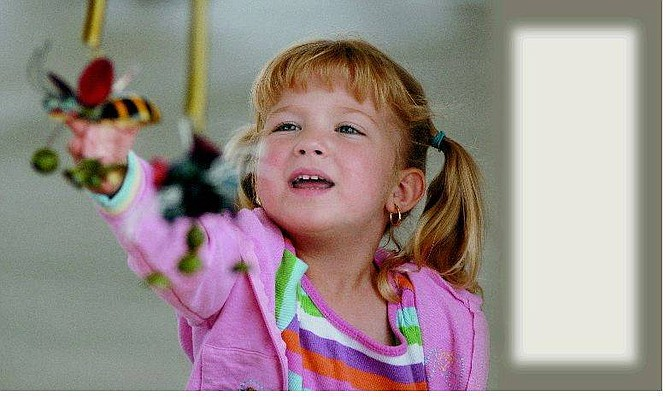 """Kevin Clifford/Nevada Appeal Camille Armstrong, 3, grabs for a bee """"hangie"""" sold by CJMV Jewelry June 9 while at the Dayton Farmers Market at Dayton Valley Floral and Nursery with her mother Suzanne."""