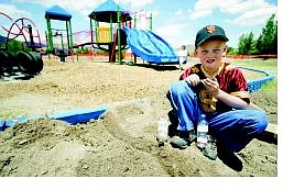 """BRAD HORN/Nevada Appeal Ryan Dunlap, 8, makes a dam in the dirt next to the new playground at Fritsch Elementary School on Saturday. Volunteers from General Electric's Sierra Nevada chapter of """"Elfun"""" worked with playground committee members to replace worn out equipment at the North Carson School."""