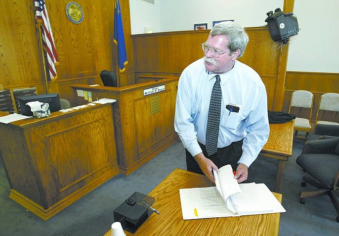 Cathleen Allison/Nevada Appeal Dayton Justice Court Judge Bill Rogers looks at a recent report on the Lyon County Corrections Master Plan in the Dayton courtroom Monday afternoon. Rogers says the rapid growth in the area is overtaxing the court system.