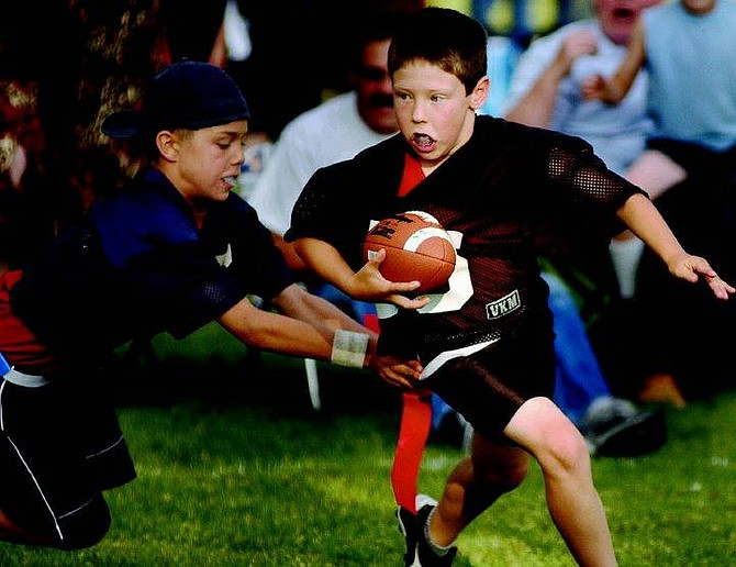 Kevin Clifford/Nevada Appeal The Raider's   Trevor Sollberger dodges a tackle from Outlaw's Tony Martini during the first half of the Carson City Youth Flag Football Leauge Division B Championship game Friday evening at Mills Park.  The Outlaws won the game 27-13.  Kevin Clifford