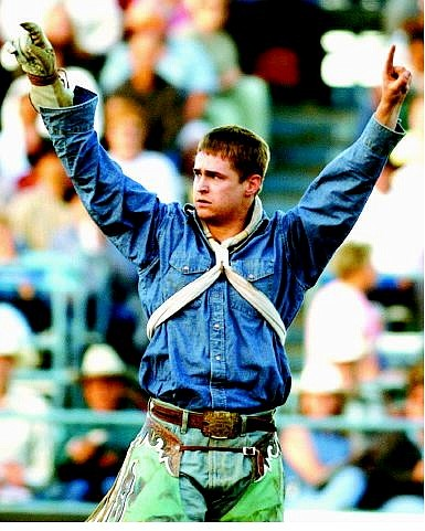 BRAD HORN/Nevada Appeal Royce Ford, of Husdson, Colo., celebrates his ride during the finals of the Reno Rodeo on Saturday. Ford split first place with Davey Shields.