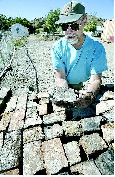 Cathleen Allison/Nevada Appeal Ron Reno talks about the plans to rebuild the Silver City Schoolhouse Wednesday afternoon. Rocks and hand-made bricks from the original 1867 construction have been saved to be used in the new building.