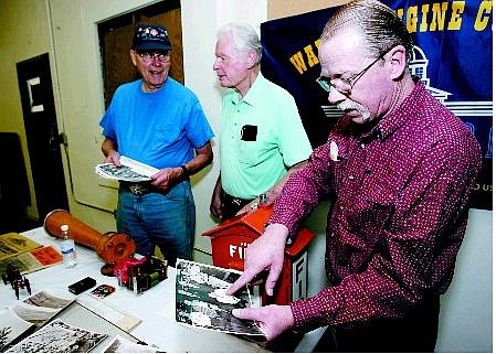 Chad Lundquist/Nevada Appeal  Veteran firefighter Kani Shannon, points to former fire chief Les Groth in a photo of the original members of the Warren Engine Company No. 1, while Les Groth, middle, and his brother George Groth, left, look over historical items from the old Warren Engine Company on Thursday.