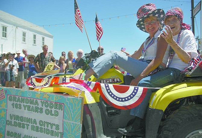 "Kevin Clifford/Nevada Appeal Virginia City Residents Katherine ""Grandma"" Yoder and Kathy Van-Nostrand drive through the  Virginia City Independence Day Celebration Parade Monday afternoon while Yoder waves to spectators.  Grandma Yoder is the oldest resident in Virginia City at 103 years old."